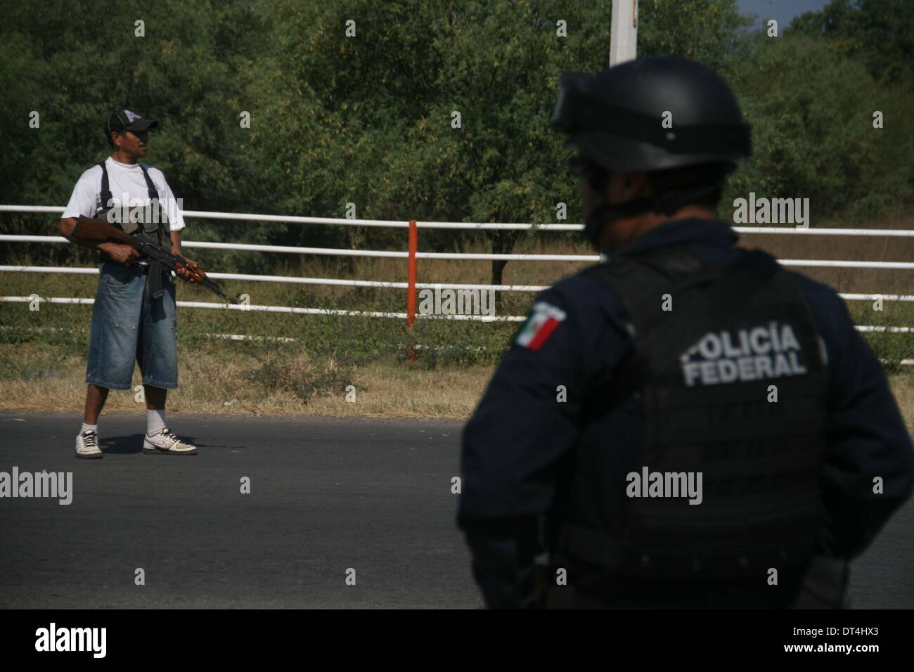 Michoacan, Mexico. 8th Feb, 2014. Federal Police officers and members of self-defense groups stands guard at a check point on a road to the municipality of Apatzingan, in Michoacan, Mexico, on Feb. 8, 2014. Members of self-defense groups entered Apatzingan on Saturday accompanied by the Mexican Army and Federal Police to take control of the town that has been affected by the actions of the criminal organization 'Los Caballeros Templarios', according to the local press. © Armando Solis/Xinhua/Alamy Live News - Stock Image
