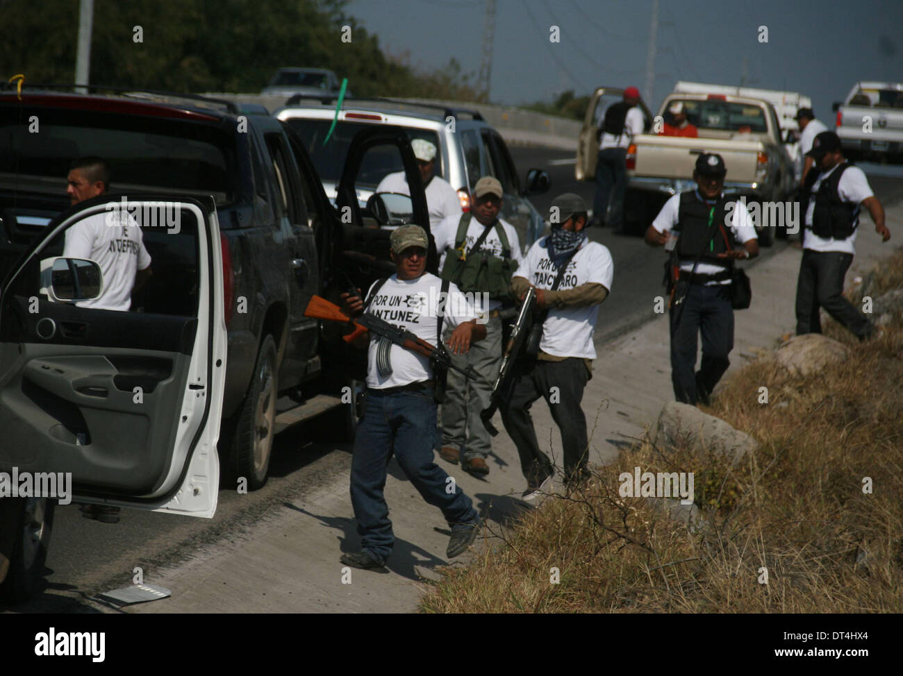 Michoacan, Mexico. 8th Feb, 2014. Members of self-defense groups react on their way to the municipality of Apatzingan, in Michoacan, Mexico, on Feb. 8, 2014. Members of self-defense groups entered Apatzingan on Saturday accompanied by the Mexican Army and Federal Police to take control of the town that has been affected by the actions of the criminal organization 'Los Caballeros Templarios', according to the local press. © Armando Solis/Xinhua/Alamy Live News - Stock Image