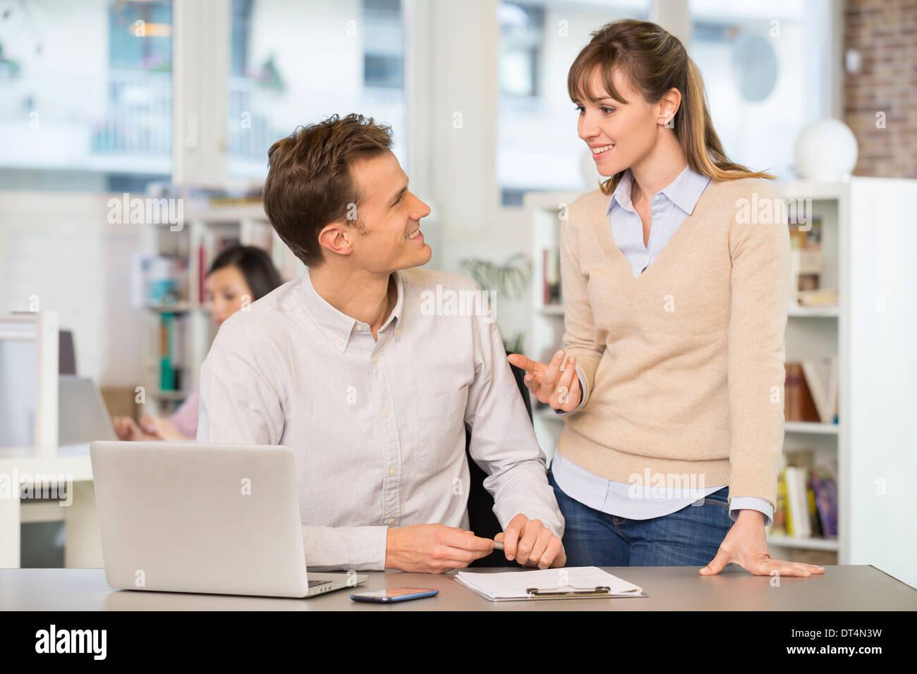 Businesswoman businessman cheerful desk speak - Stock Image