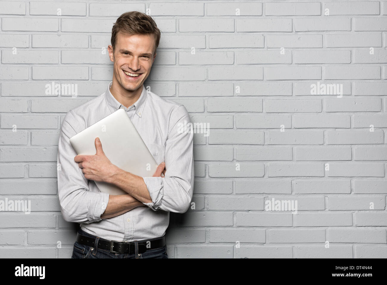 Male portrait smiling computer studio brick looking camera - Stock Image