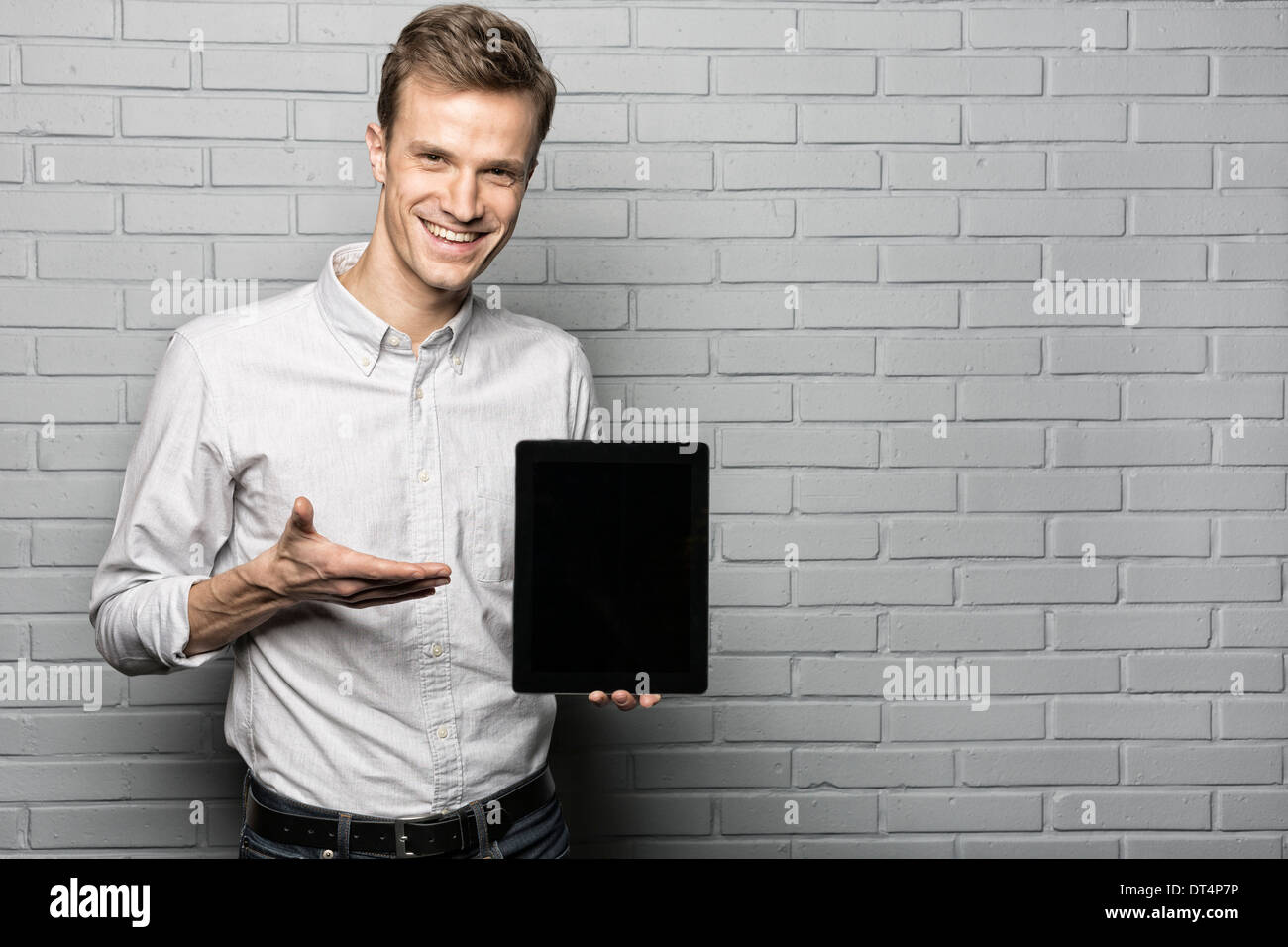 Portrait of male model presenting tablet on studio with gray background, looking camera Stock Photo