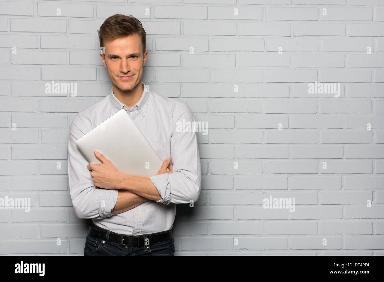 Portrait of cheerful Male holding computer, studio grey background looking camera Stock Photo