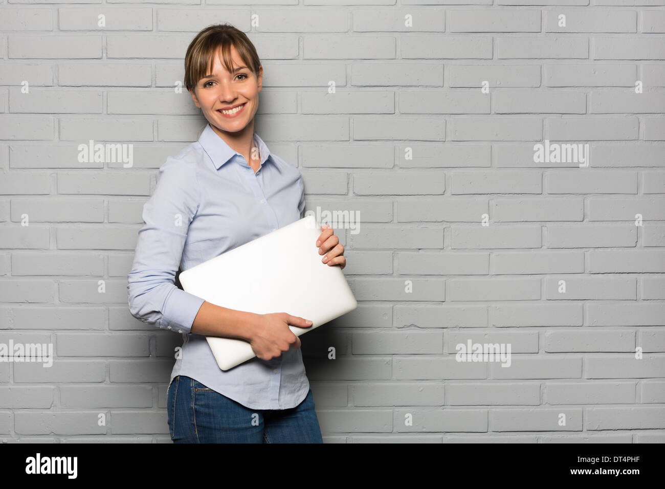 Portrait of young woman with computer in studio, looking camera - Stock Image