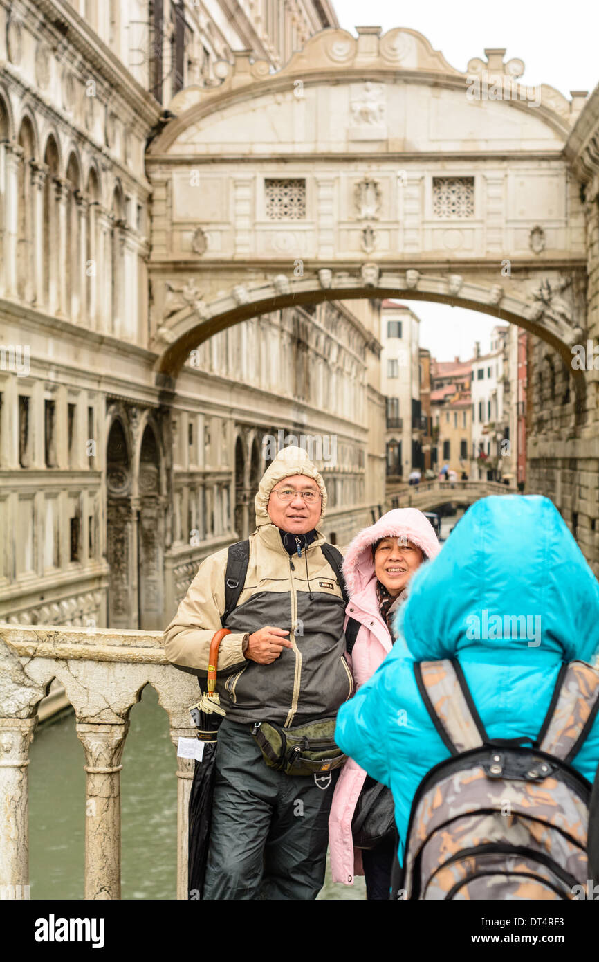 Venice, Italy. Elderly Asian couple, tourists in wet weather clothing, posing for pictures in front of the Bridge of Sighs. - Stock Image