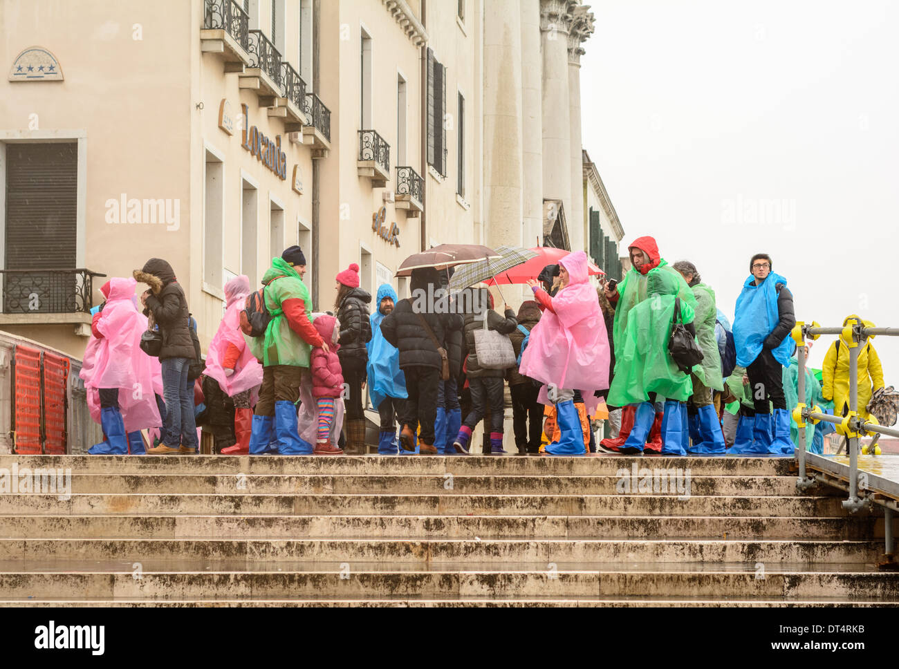 Venice, Italy. Tourists and children in wet weather clothing and rain boots, standing on a bridge during rain. - Stock Image