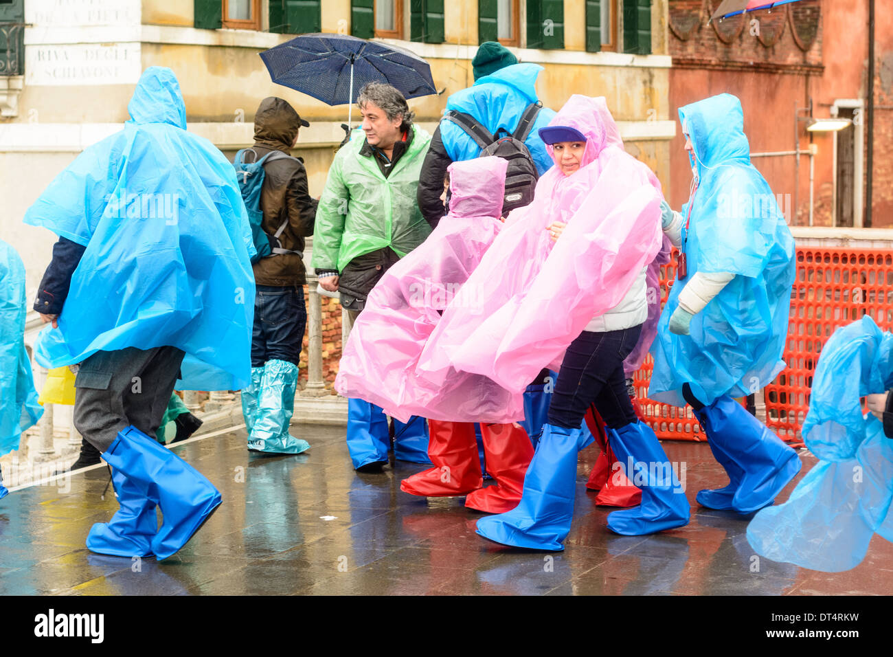 Venice, Italy. People in wet weather clothing, rain ponchos, and rain boots, standing on bridge during rain. - Stock Image