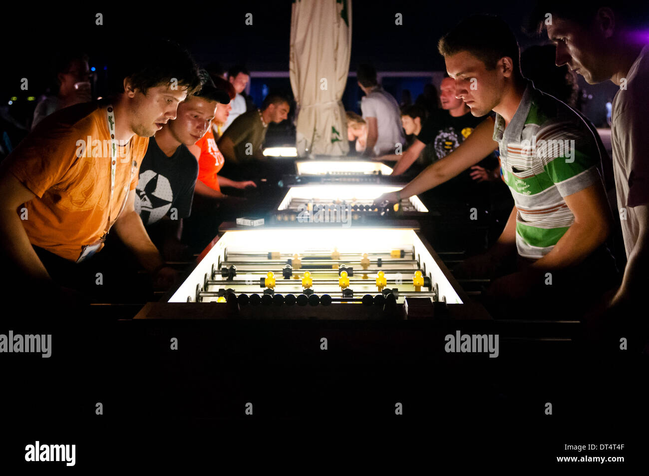 Young group of people playing and enjoying table football at night at Bažant Pohoda festival, Trenčín, Slovakia - Stock Image