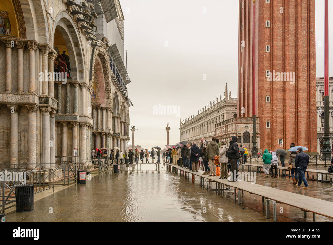 Venice, Italy. Tourists on acqua alta (high water) gangways queuing to enter the San Marco Basilica. - Stock Image