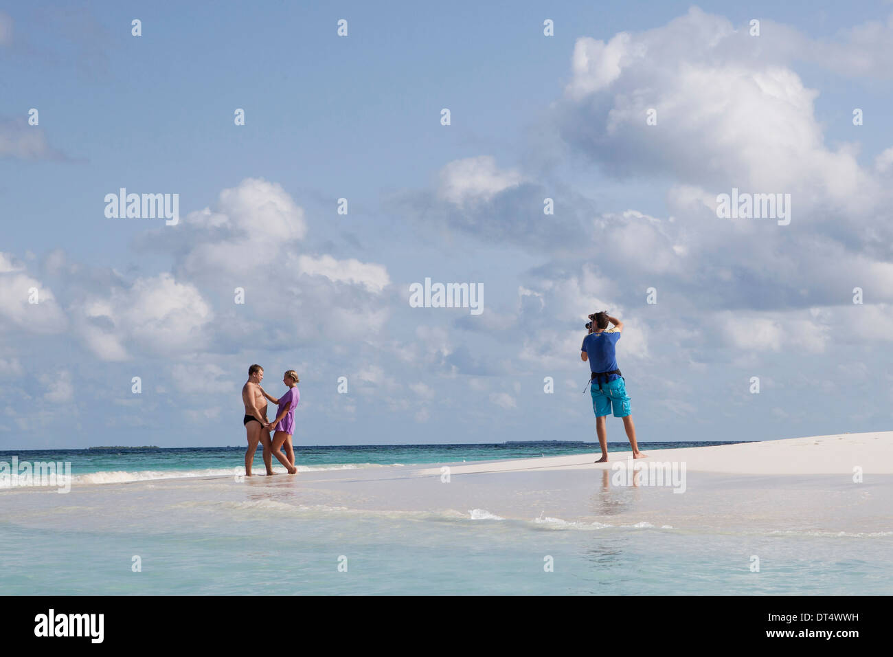 A couple on a beach being photographed in The Maldives - Stock Image