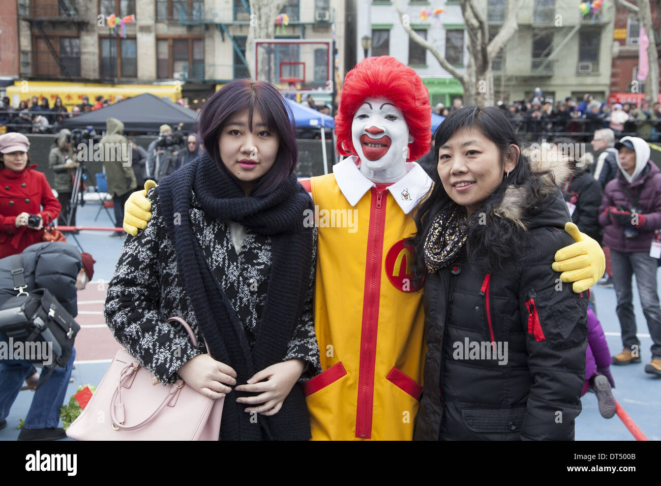 Ronald McDonald with 2 young ladies at the Chinese New Year celebration in Chinatown, NYC. - Stock Image