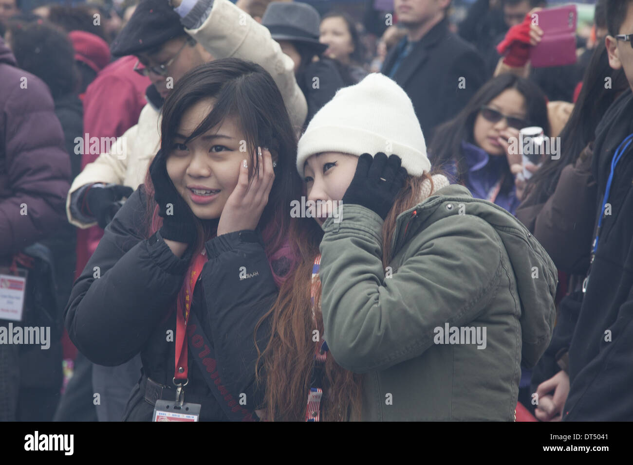 Teenage girls hold their ears at the Chinese New Year firecracker ceremony in NYC. - Stock Image
