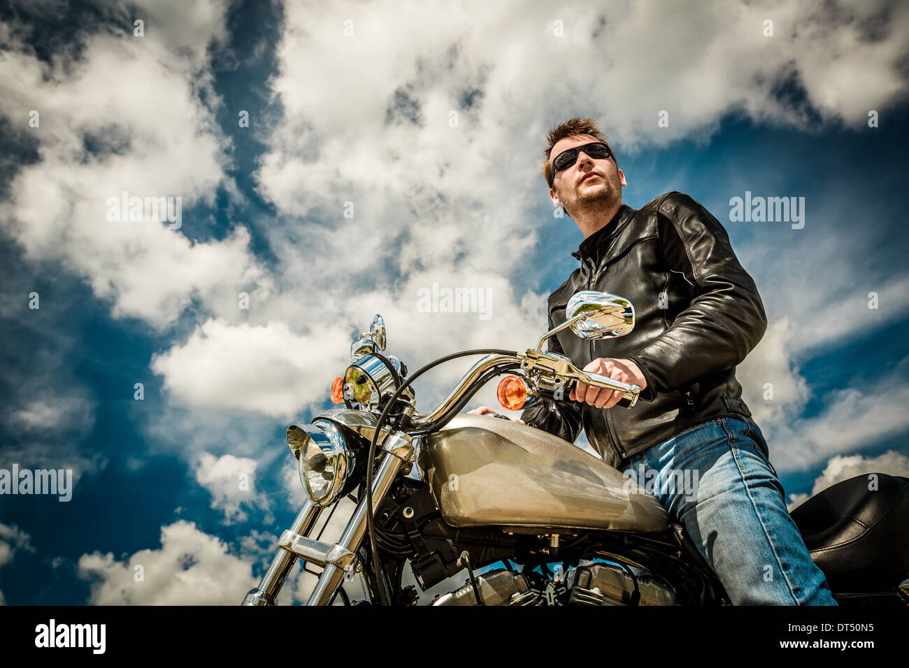 Biker man wearing a leather jacket and sunglasses sitting on his motorcycle looking at the sunset. - Stock Image