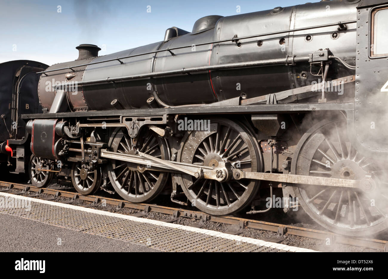 A steam train increasing steam ready to depart from a station - Stock Image