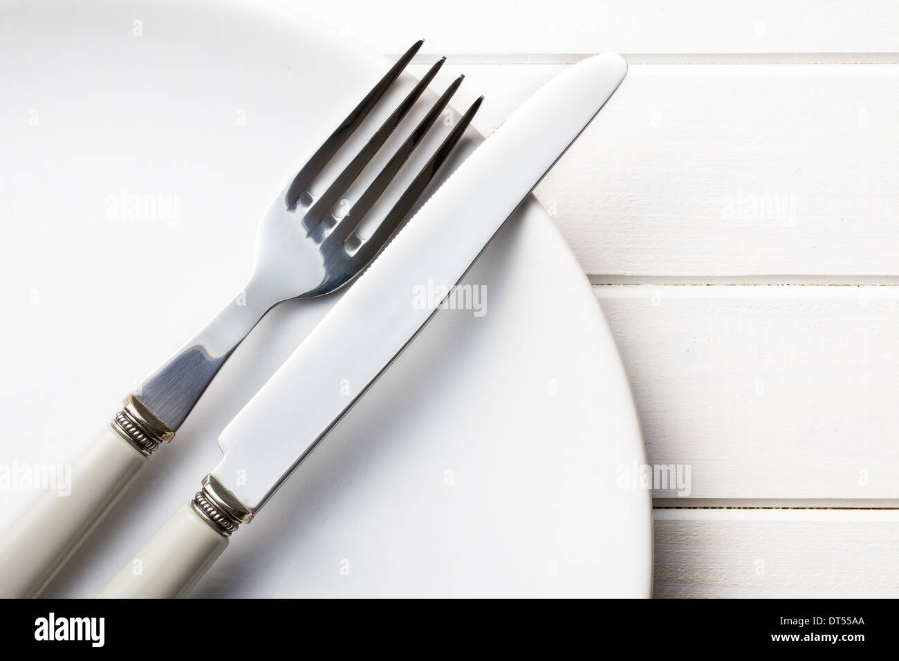 plate with cutlery on kitchen table - Stock Image