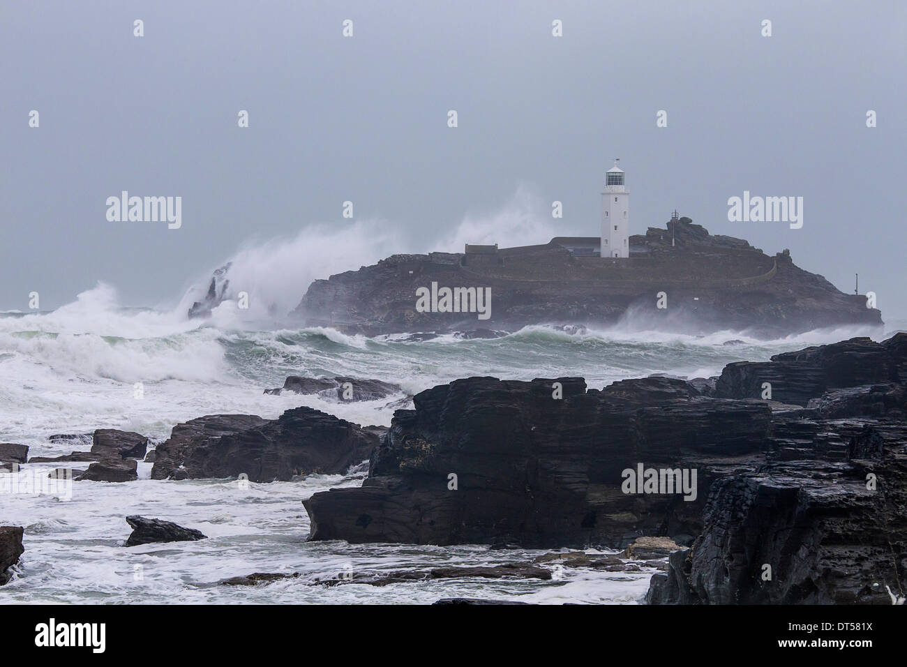Sennen, UK. 8th Feb, 2014. Godrevy in Cornwall gets battered by huge waves, high winds and storms on saturday 8th febuary Credit:  bowen oakley/Alamy Live News - Stock Image