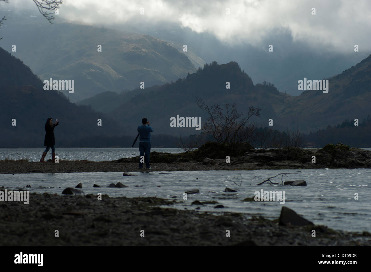 A couple taking pictures of each others and of the beautiful Borrowdale backgound in the Lake District. - Stock Image