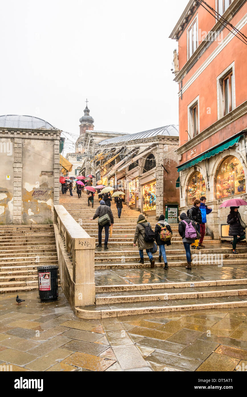 Venice, Italy. People with umbrellas and wet weather clothing crossing the Rialto Bridge at a rainy day, overcast Stock Photo