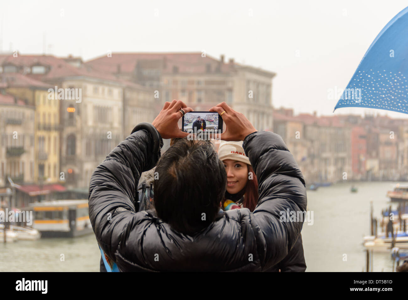 Venice, Italy. View over the Grand Canal through the display of a smartphone from a man taking pictures from an Asian couple. - Stock Image