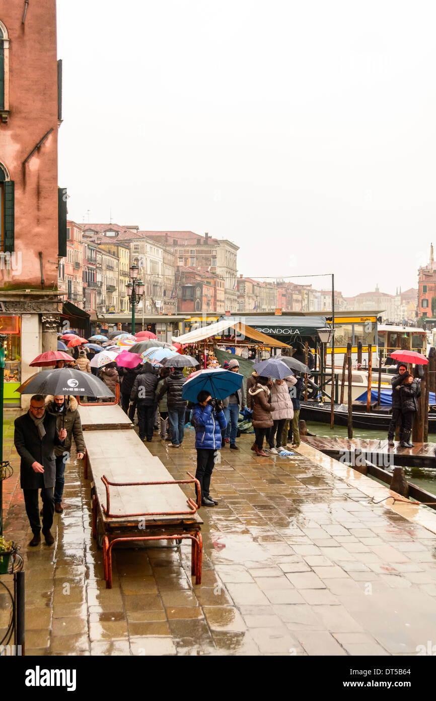 Venice, Italy on a rainy day, preparing for acqua alta (high water) with gangways on the walkway and people queuing Stock Photo