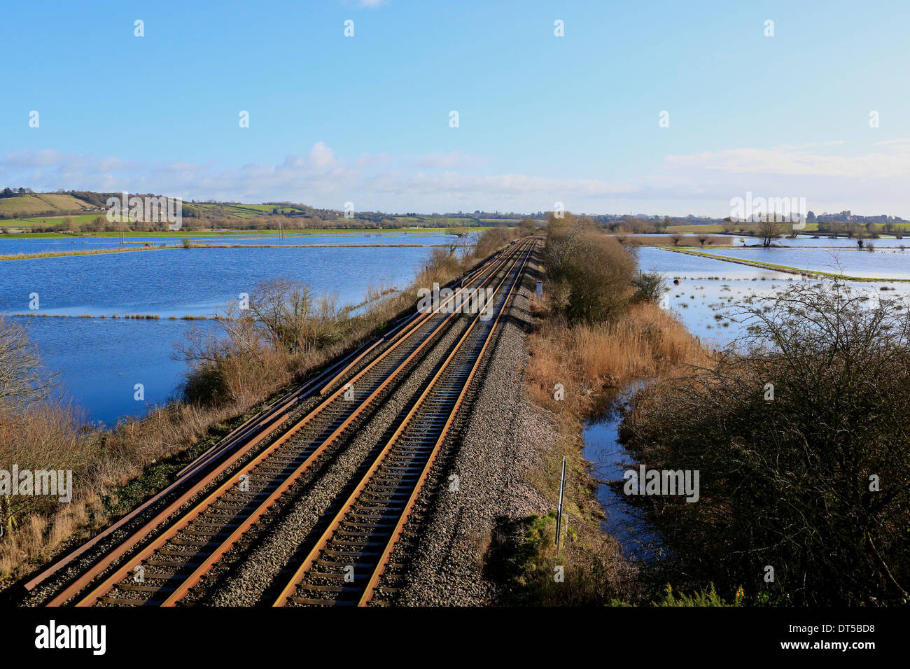 Flooding UK, Somerset Levels 2014. Rail line surrounded by flooded farm land on West Sedge Moor - Stock Image