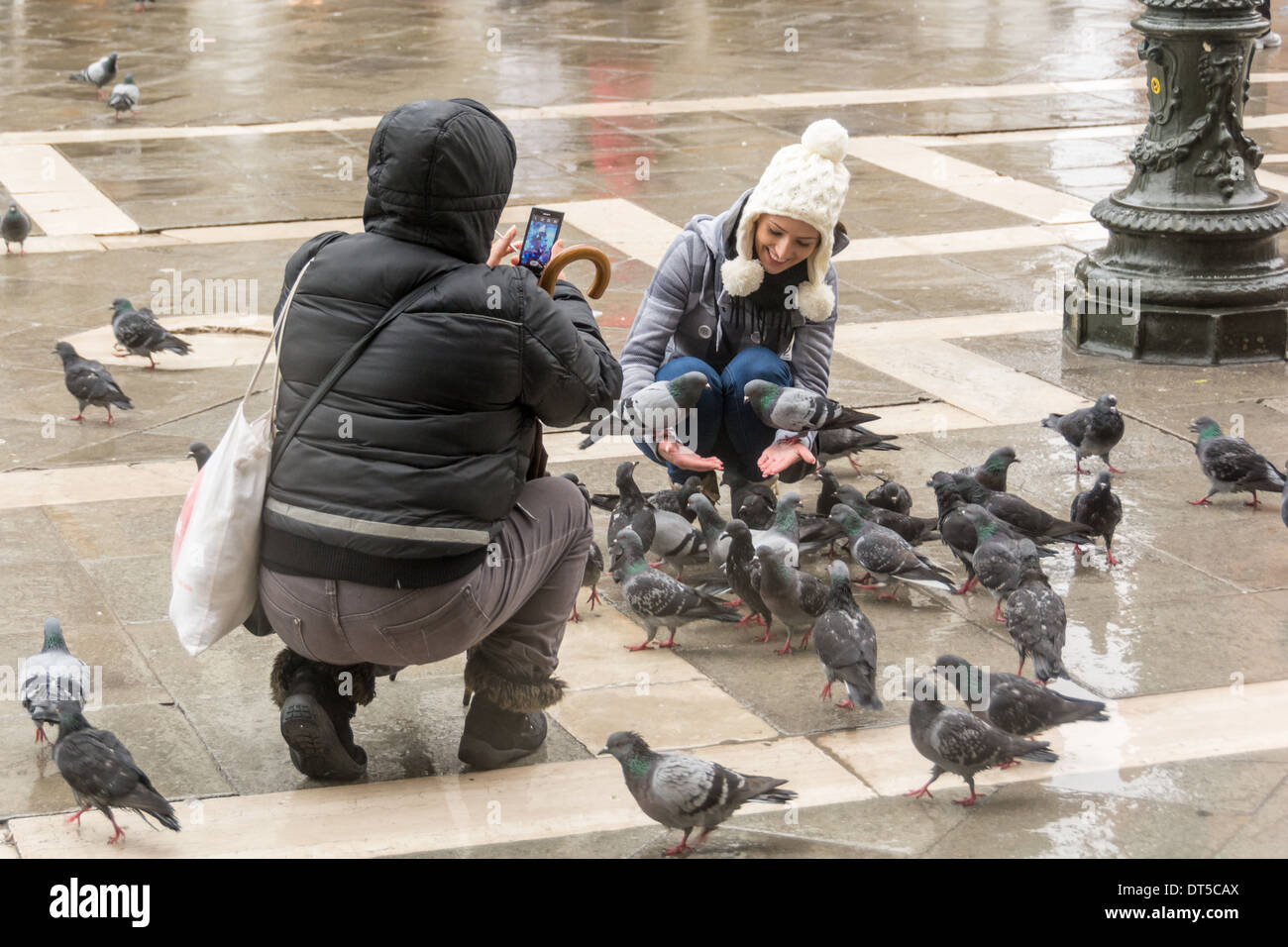 Venice, Italy. Pretty young smiling women with pigeons on her arms, photographed by a man with smartphone on St Stock Photo