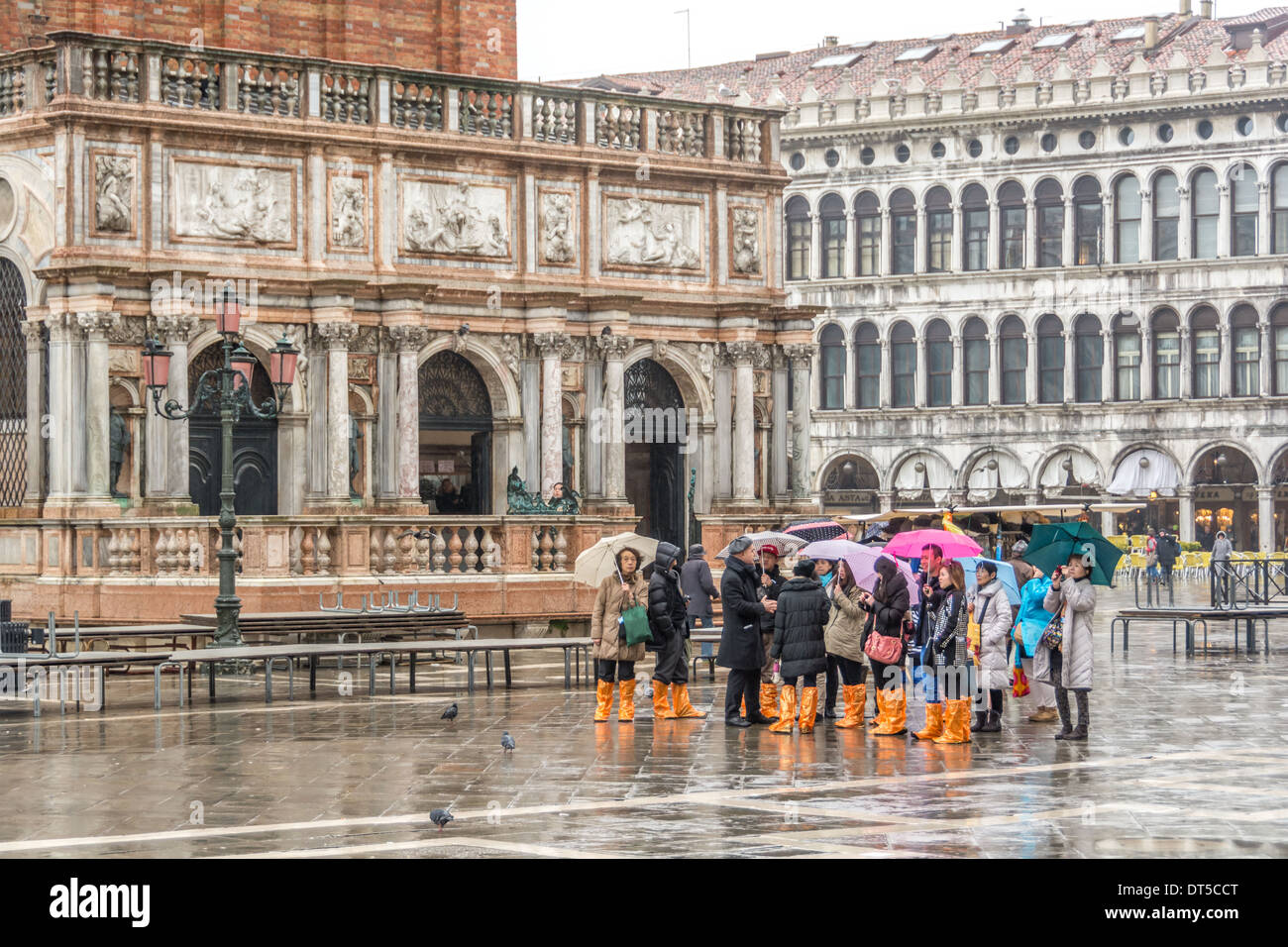 Venice, Italy. Asian tourists in wet weather clothing, umbrellas, and orange rain boots on St Mark´s Square, Campanile Stock Photo