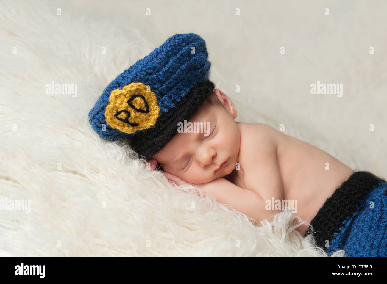 Sleeping 12 day old newborn baby boy wearing a blue and gold crocheted  police officer s hat. 70ab723b359c