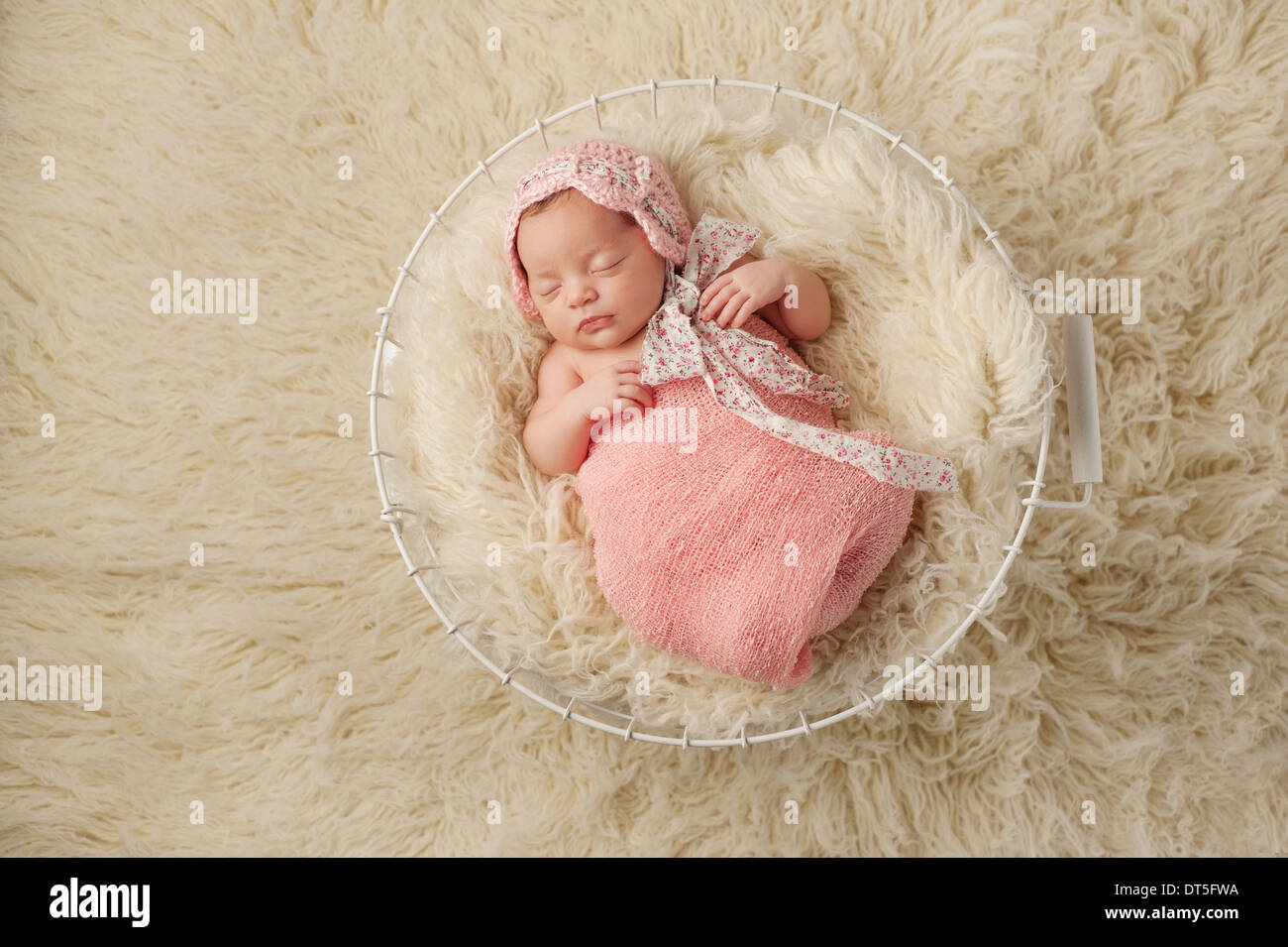 A portrait of a five week old newborn baby girl wearing a pink bonnet and  sleeping in a wire basket. Shot from overhead. 03bd5d5ef68