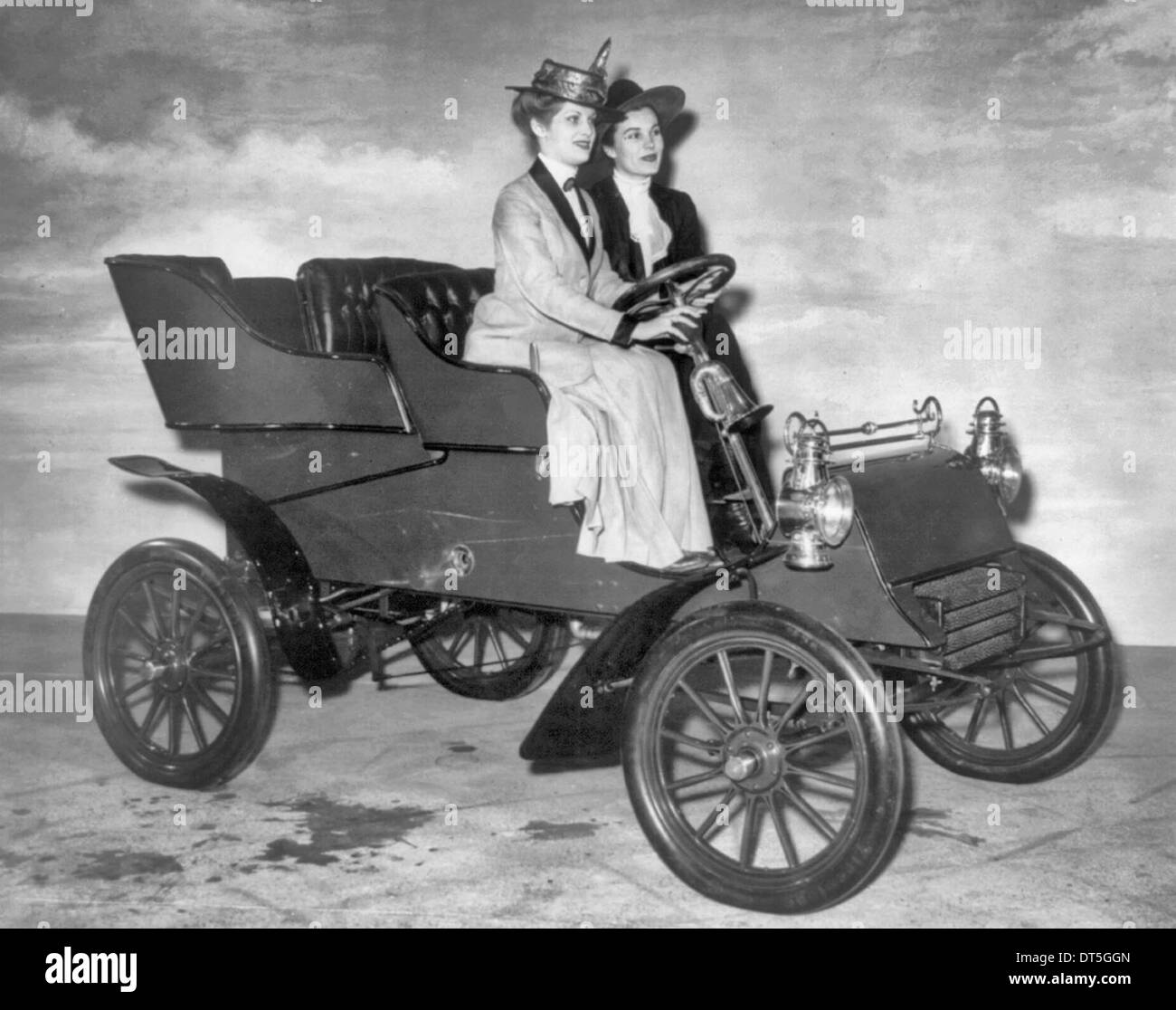 Two women sitting in display model of 1903 Ford automobile at the Automotive Industry Golden Jubilee in 1946; woman behind wheel has hand on car horn. - Stock Image