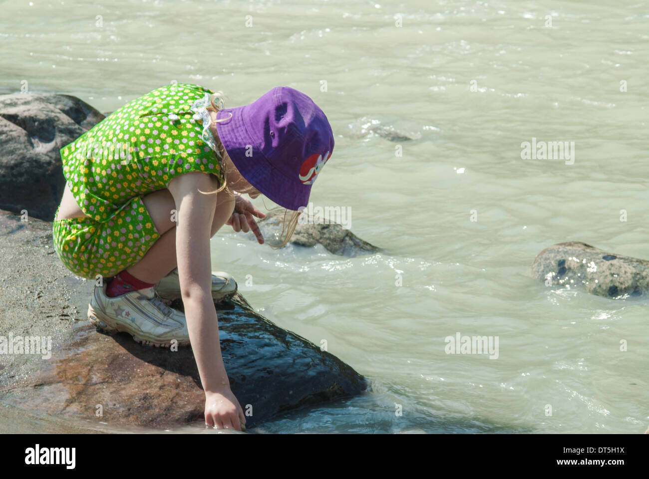 Young girl crouched along the Athabasca River looking for aquatic life, Jasper National Park Alberta Canada - Stock Image