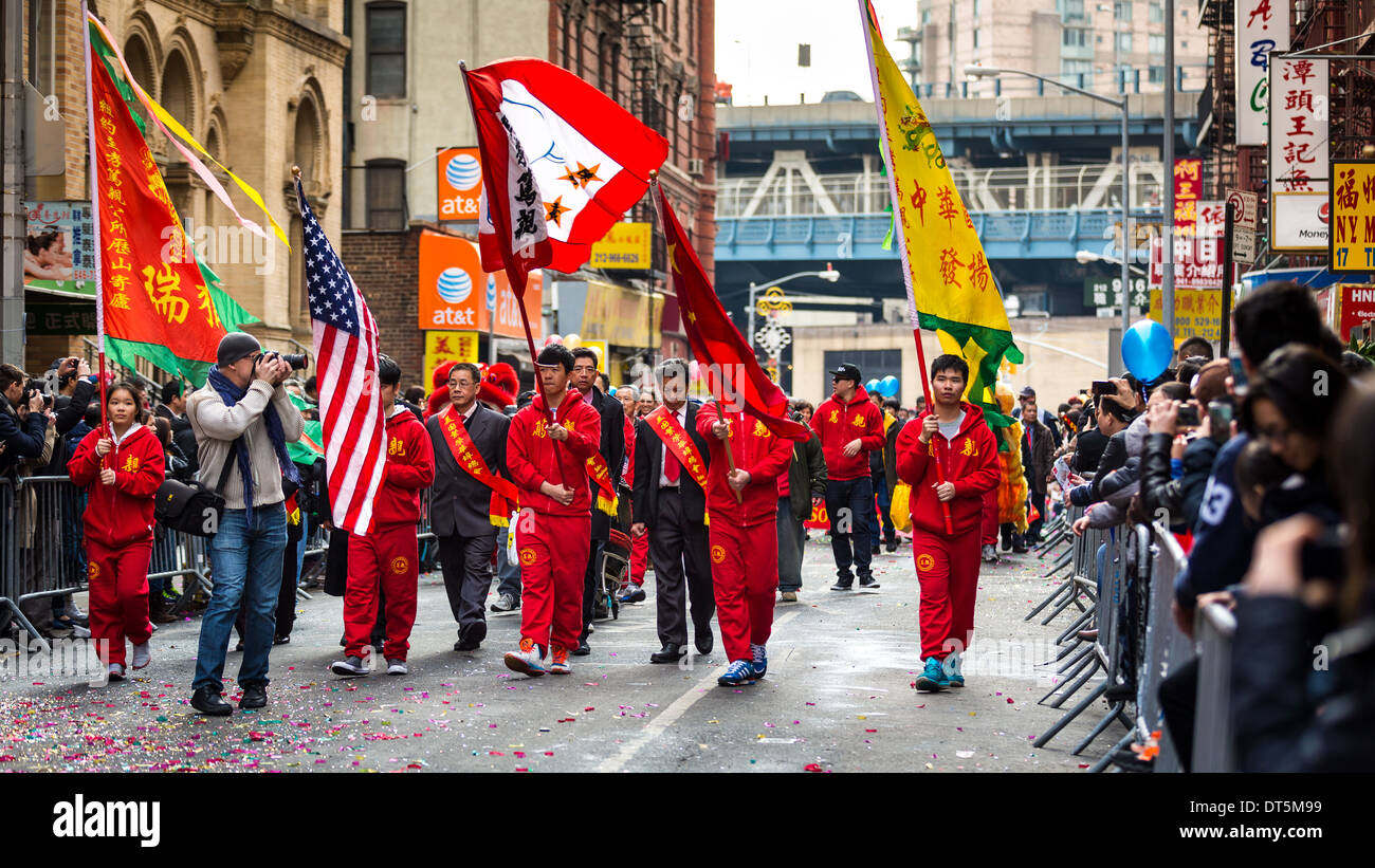 Lunar New Year Festival celebrated in Manhattan's Chinatown. Young men dressed in red costumes carry flags. - Stock Image