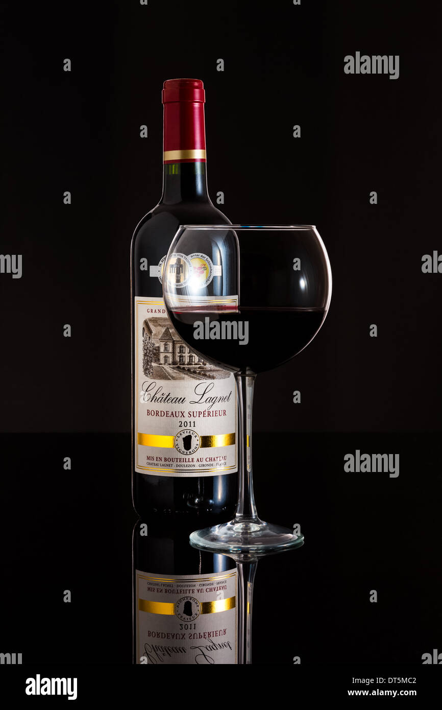 Glass and Bottle of 2011 Chateau Lagnet wine. - Stock Image