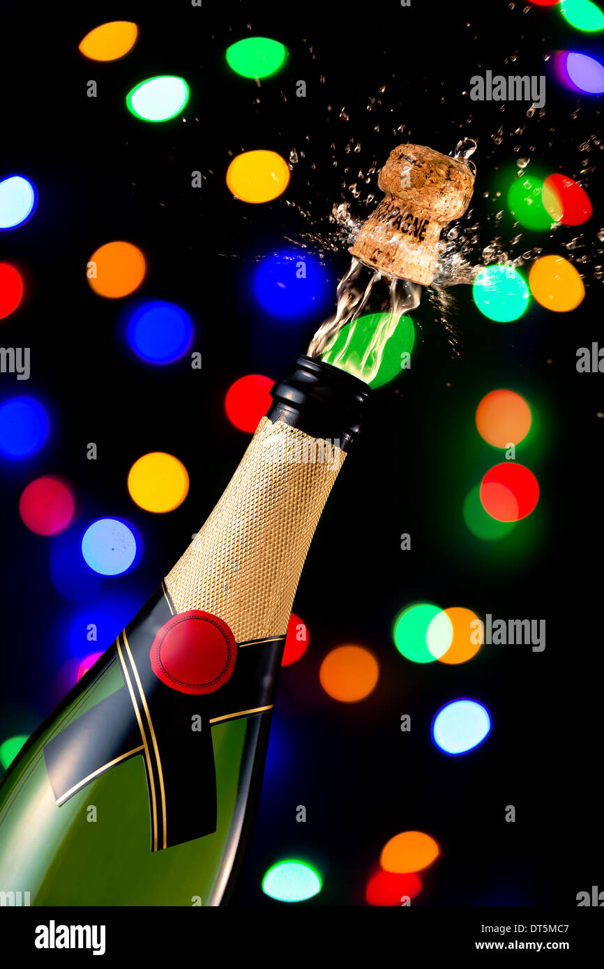 Popping cork on a champagne bottle - Stock Image