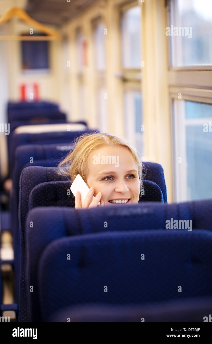 Smiling woman talking on the phone in train. - Stock Image