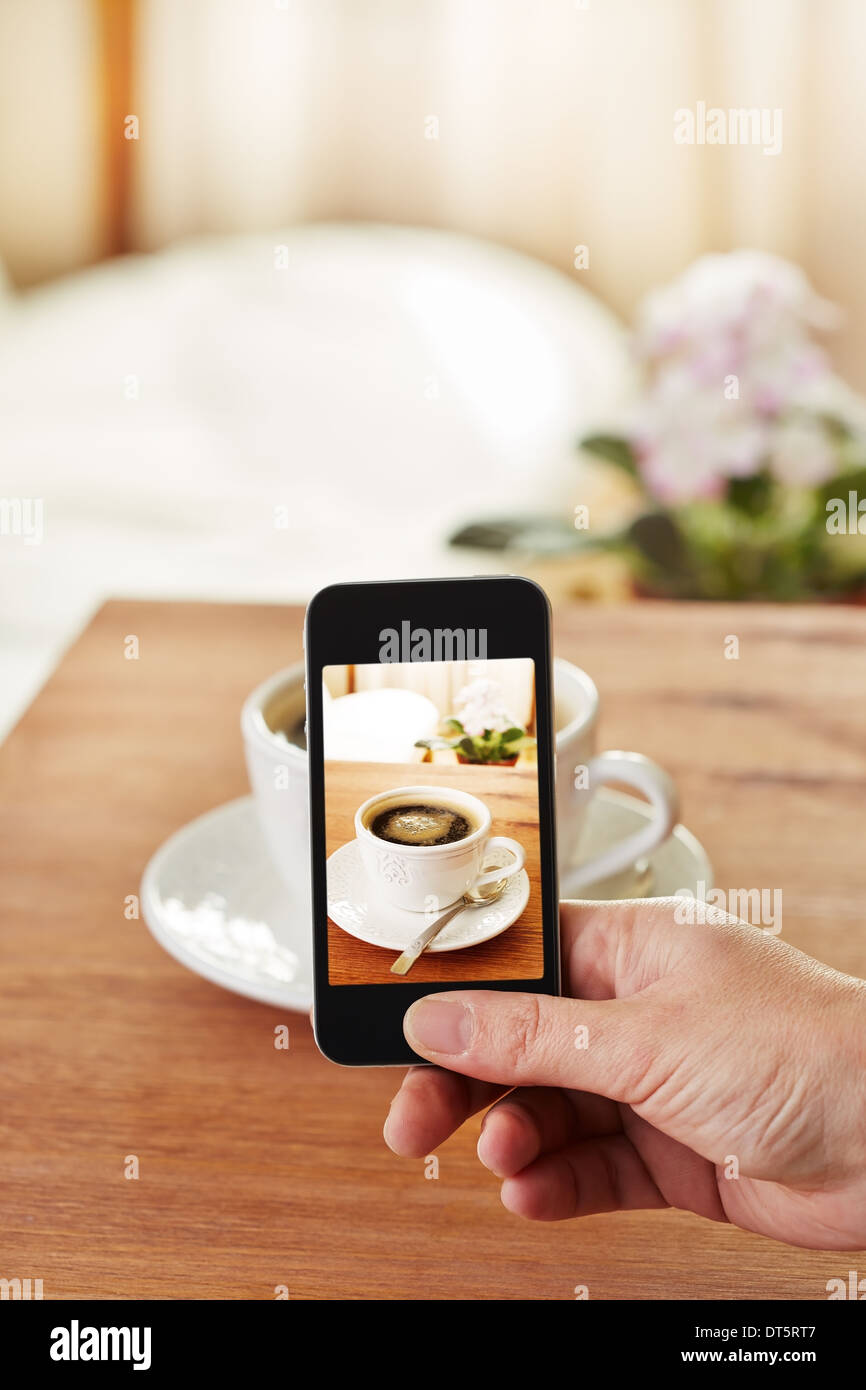 Smartphone taking picture of coffee in a bar - Stock Image