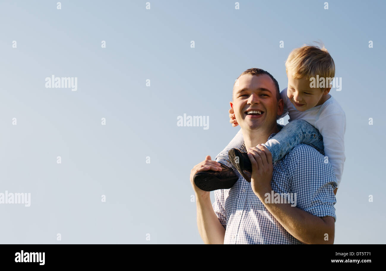 Young father giving his son a piggy back ride - Stock Image