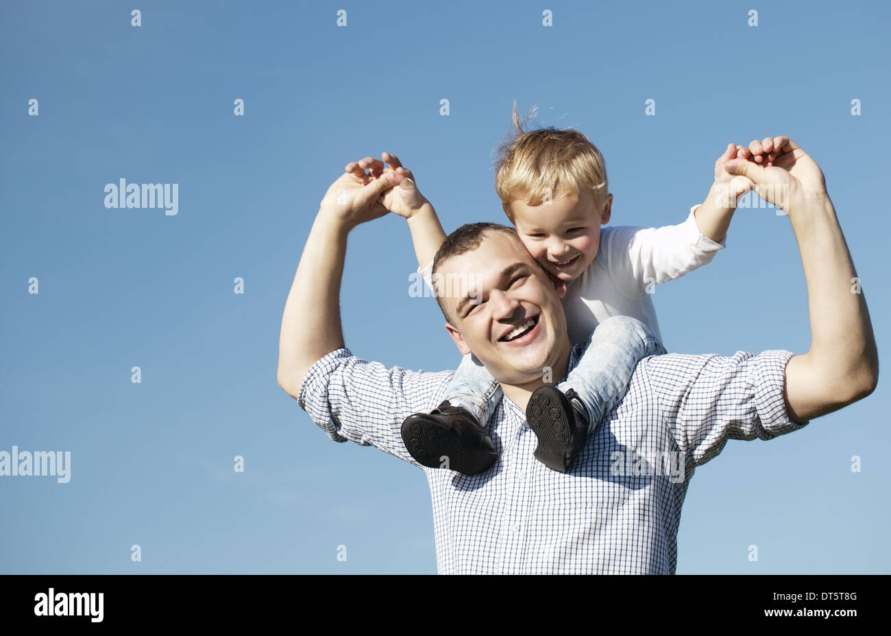 Dad giving his young son a piggy back ride - Stock Image