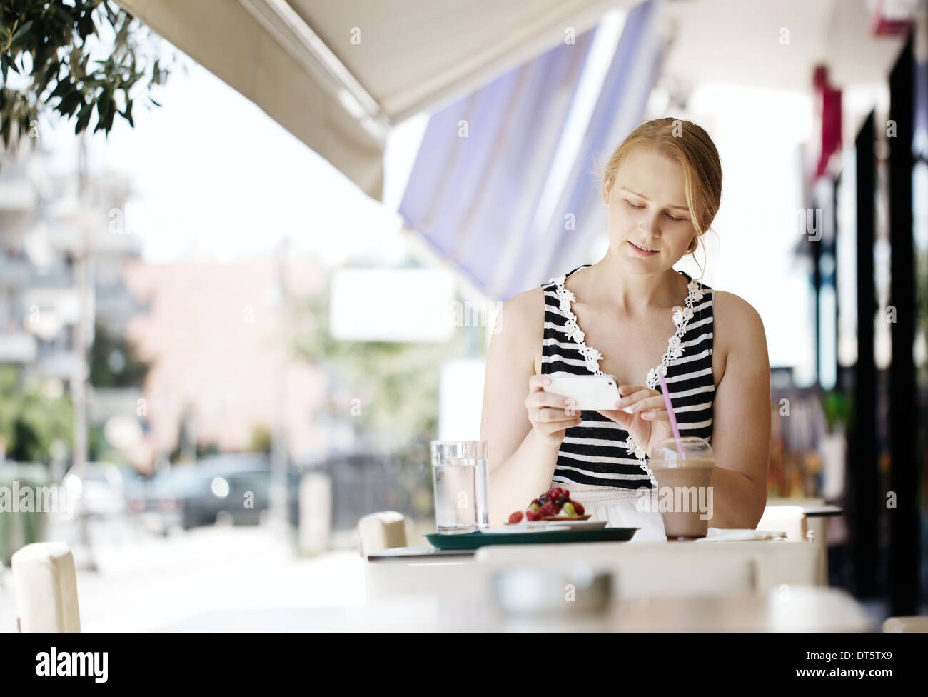 Attractive woman taking picture of a pastry on her mobile - Stock Photo