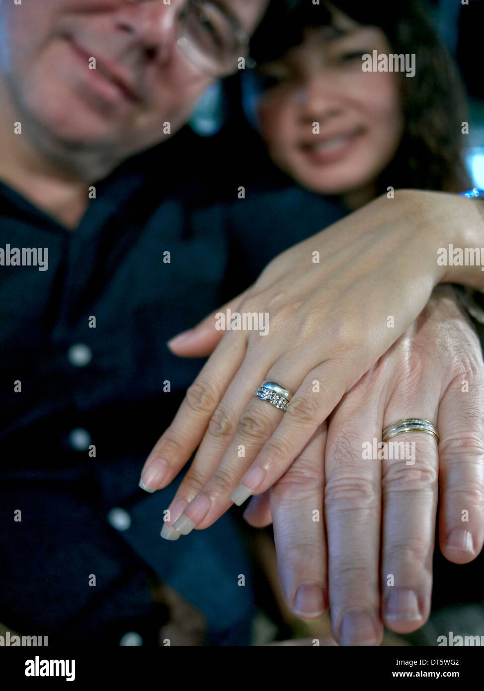 Newly wed young couple proudly displaying wedding rings. - Stock Image