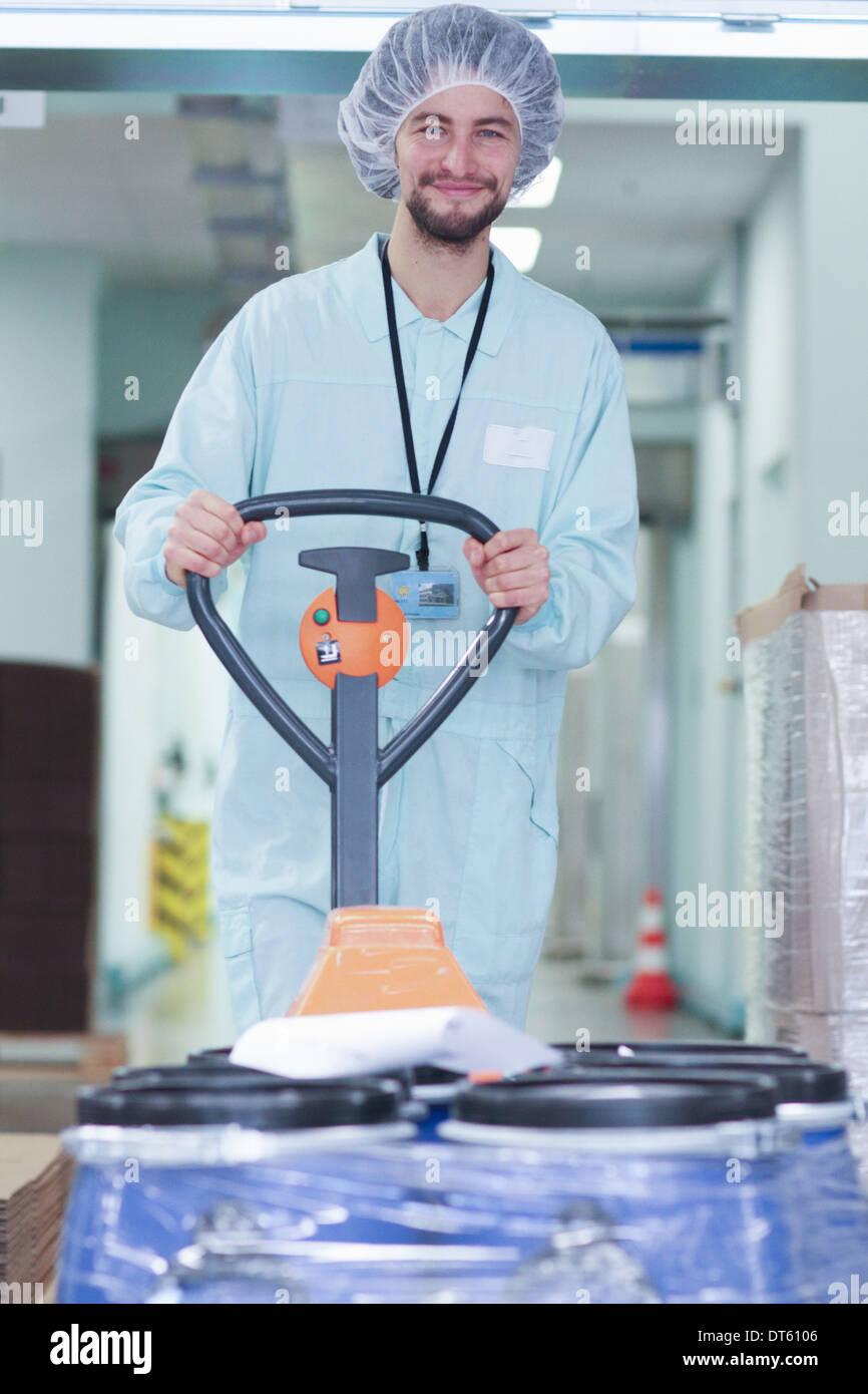 Laboratory technician moving containers - Stock Image