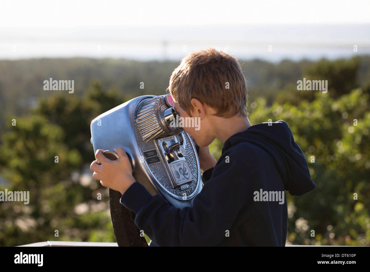 Boy using coin operated binoculars - Stock Image
