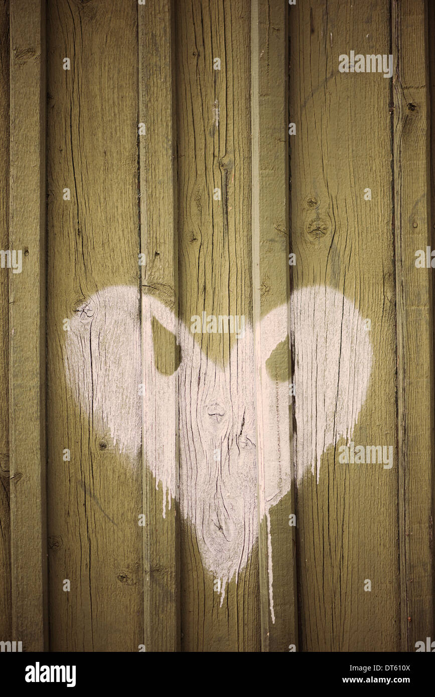 White heart with evil eyes painted on wooden wall of building - Stock Image