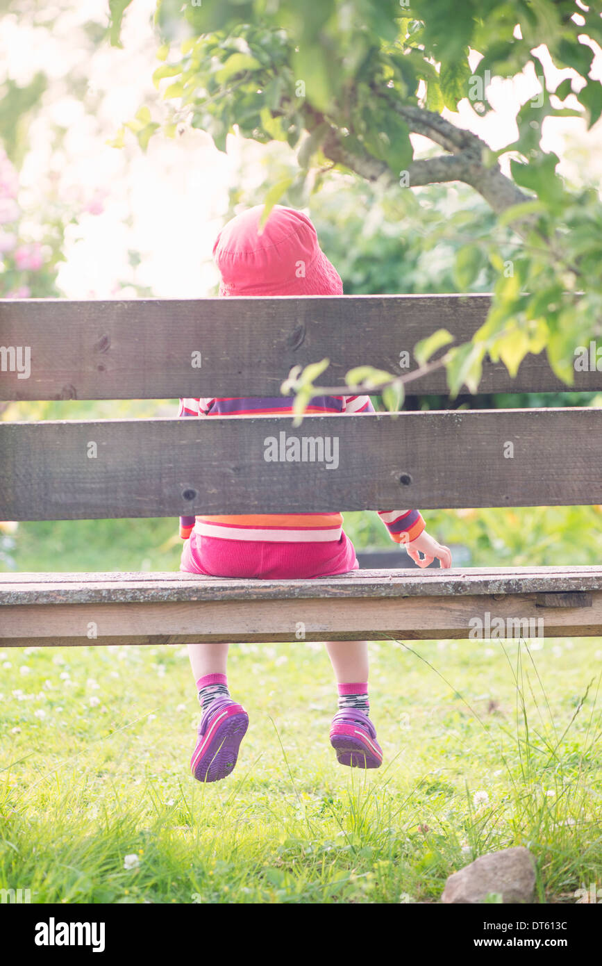 Tranquil summer scene. Young girl sitting alone in garden, watching plants and flowers. Stock Photo