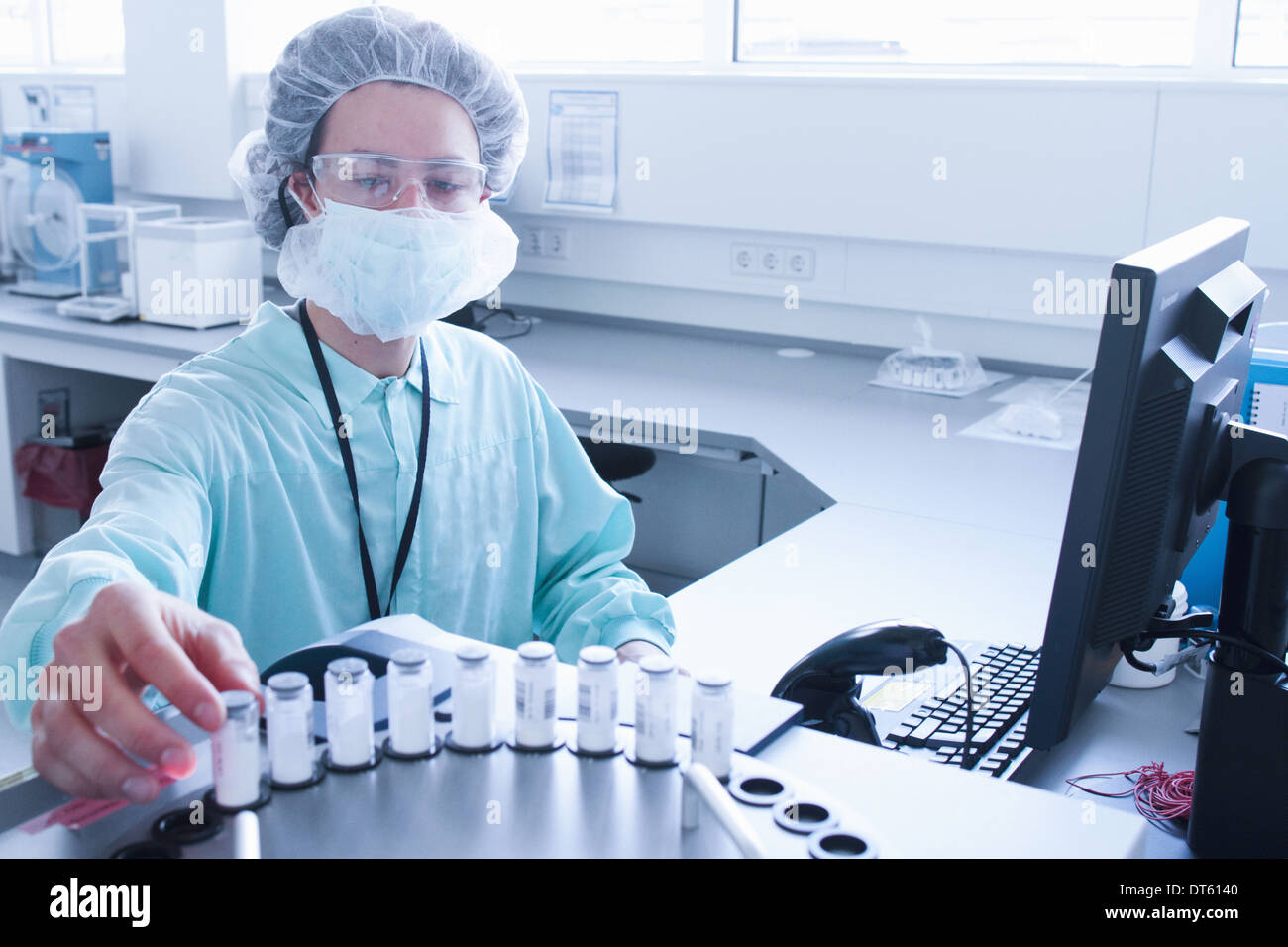 Laboratory technician placing containers into carousel - Stock Image