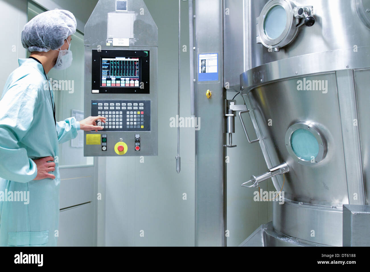 Laboratory technician checking and adjusting equipment reading - Stock Image
