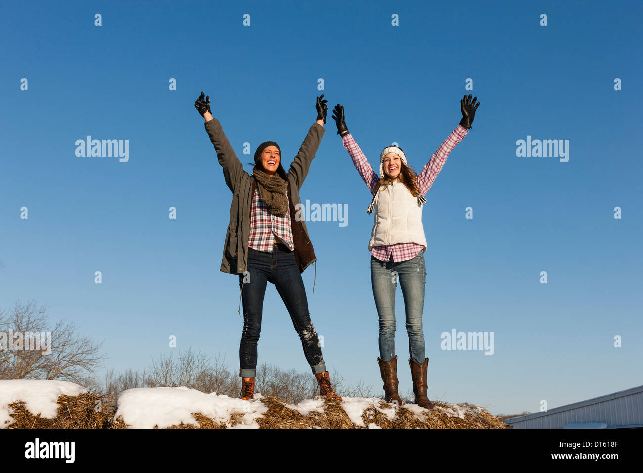 Two young women with arms raised on winter hilltop - Stock Image