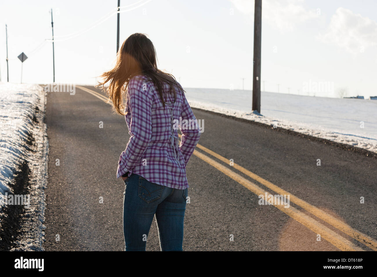 Young woman walking up remote road in winter Stock Photo