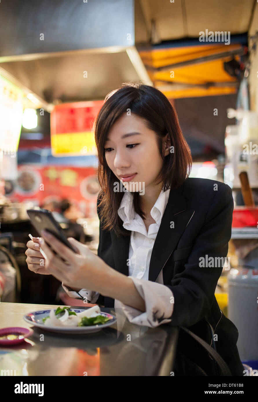 Businesswoman using cellular phone, night market, Taipei, Taiwan - Stock Image