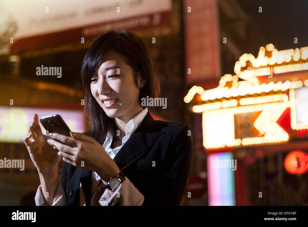 Businesswoman using cellular phone, night market, Taipei, Taiwan - Stock Image