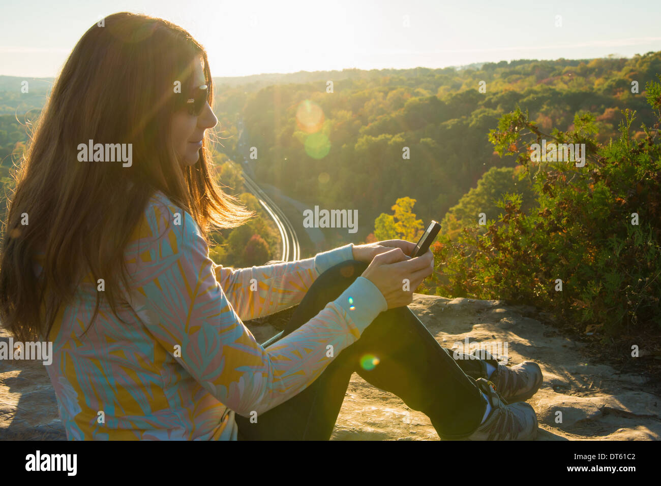Mid adult woman sitting on elevated rock using mobile phone - Stock Image